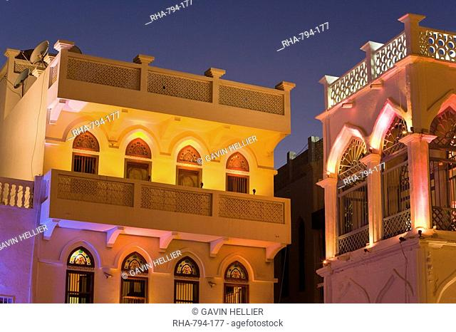 Colourfully illuminated latticed houses along the corniche, Mutrah, Muscat, Oman, Middle East