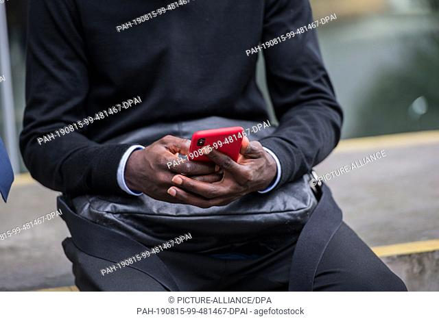15 August 2019, Hessen, Frankfurt/Main: Bakery Jatta (HSV) sits on a wall on the DFB premises and operates his smartphone