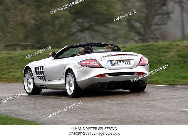 Mercedes SLR McLaren, model year 2008-, silver, driving, diagonal from the back, rear view, country road, open top