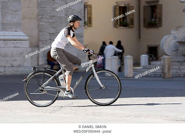 Italy, Arco, Mid adult woman riding electric bicycle