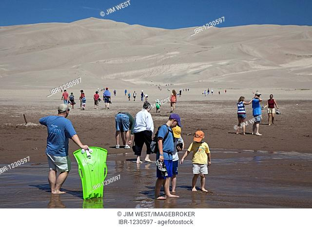 Vacationers along Medano Creek in Great Sand Dunes National Park, Mosca, Colorado, USA