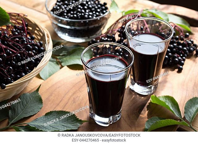 Two glasses of elderberry syrup, with fresh elderberries in the background