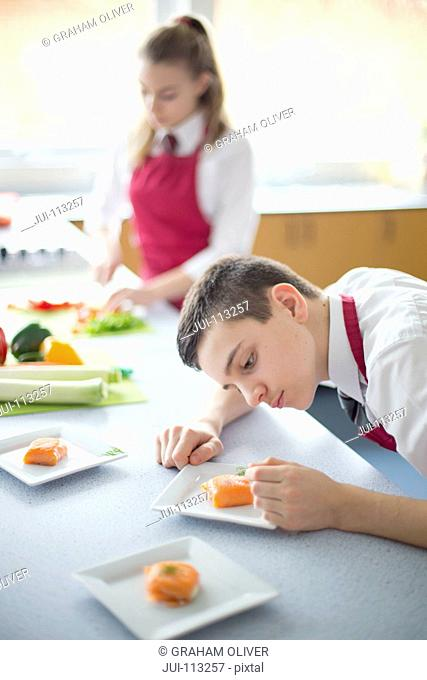 Focused male high school student plating food in home economics class