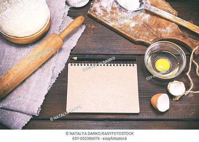 paper notepad with black pencil and dough with ingredients on a brown wooden table, vintage toning