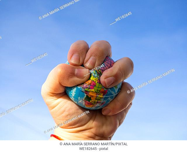 A person destroying with his hand a terrestrial globe or planet earth. Concept of ecology