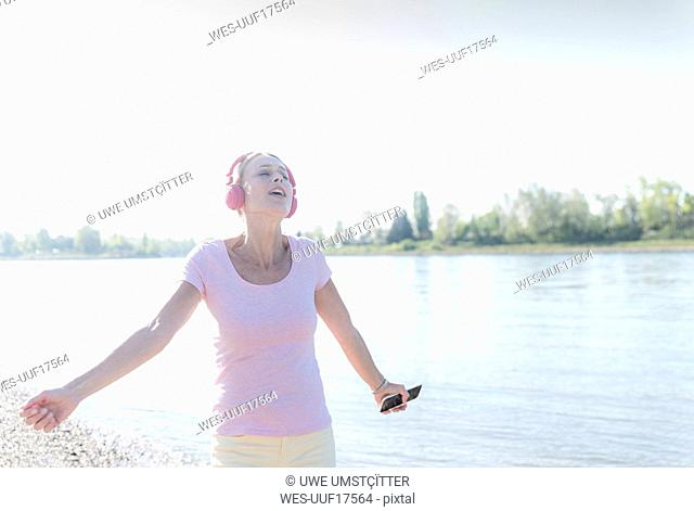 Happy mature woman listening to music with headphones at the riverside