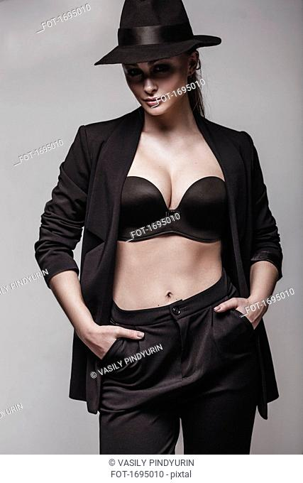 Portrait of seductive woman standing with hands in pockets against gray background