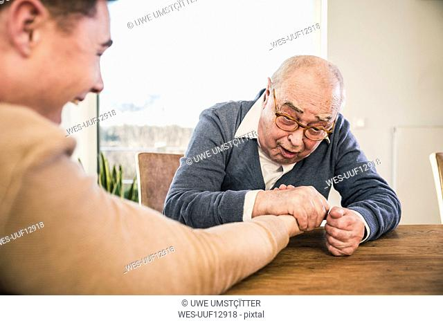 Senior man and young man arm wrestling