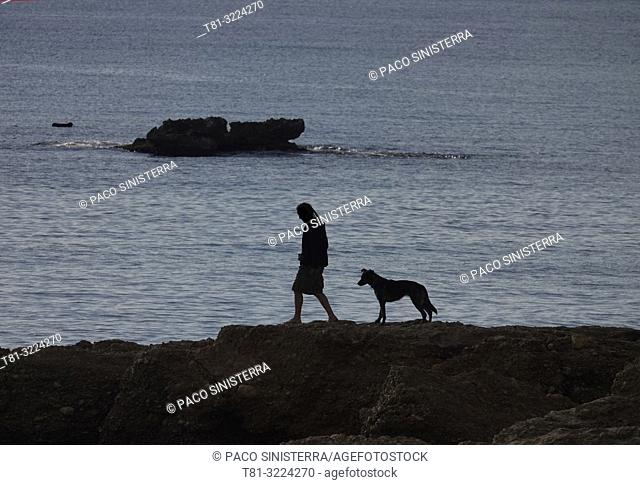 Silhouette of man with dog on the beach. Almeria province, Andalusia, Spain