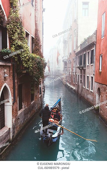 Elevated view of gondolier on misty canal, Venice, Italy