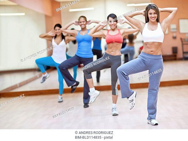 Hispanic women taking exercise class in gym
