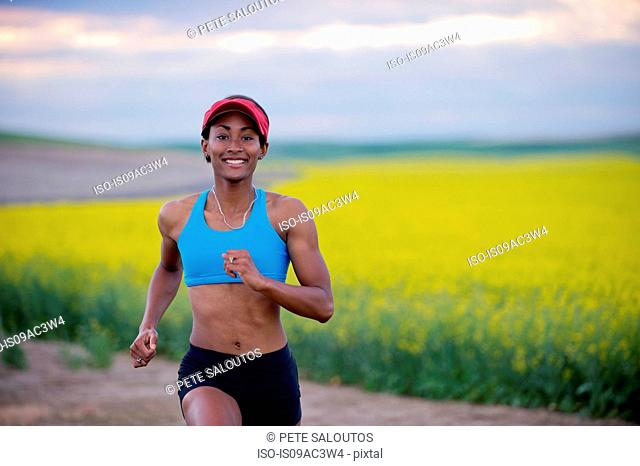 Young woman running down dirt track