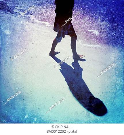 Person walking along the ocean shoreline