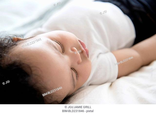 Mixed Race baby boy sleeping on bed