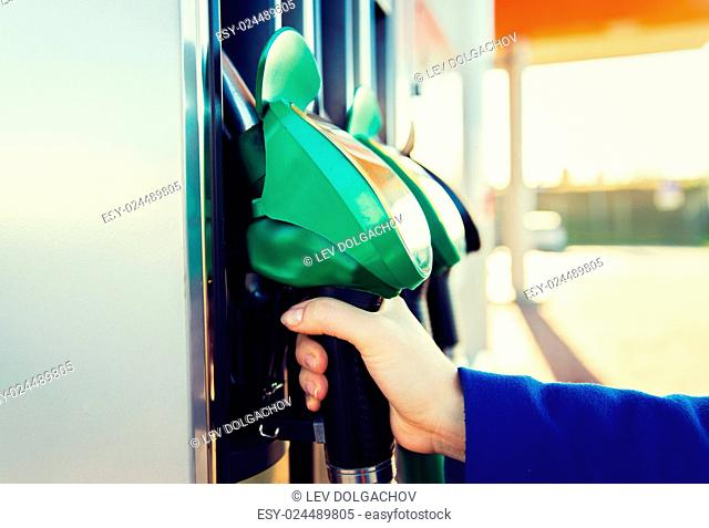 object, fuel, oil, tank and transport concept - close up of hand holding gasoline hose at gas station