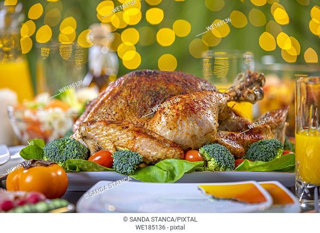 Celebrating Thanksgiving with roasted turkey on festive table. Roasted turkey on festive table for Thanksgiving celebration