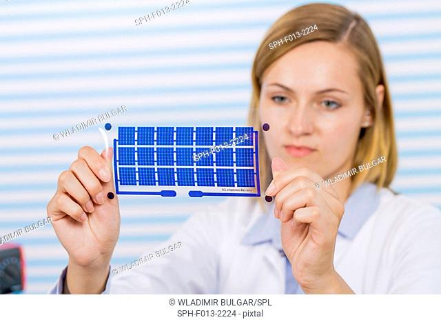 Female technician holding thin film solar cells