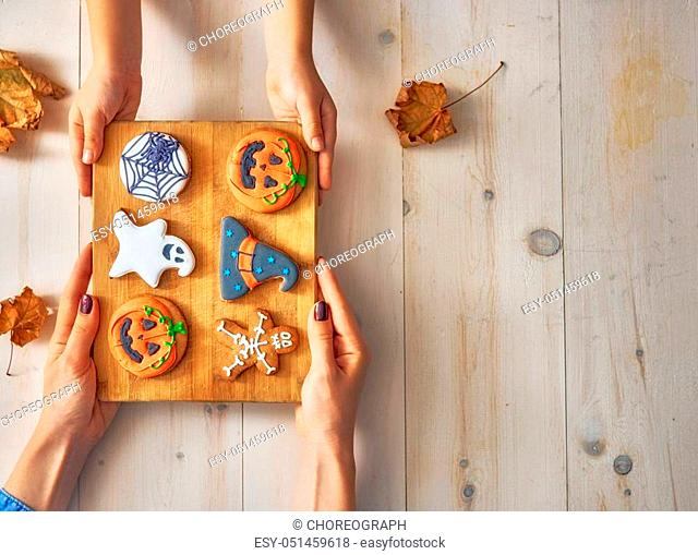 Happy halloween! A mother and daughter having festive sweets on the table in the home. Family preparing for holiday. Top view. Close up