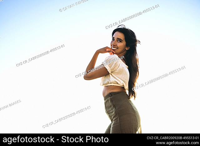 Young Latina Woman smiling by the ocean at golden hour in summertime