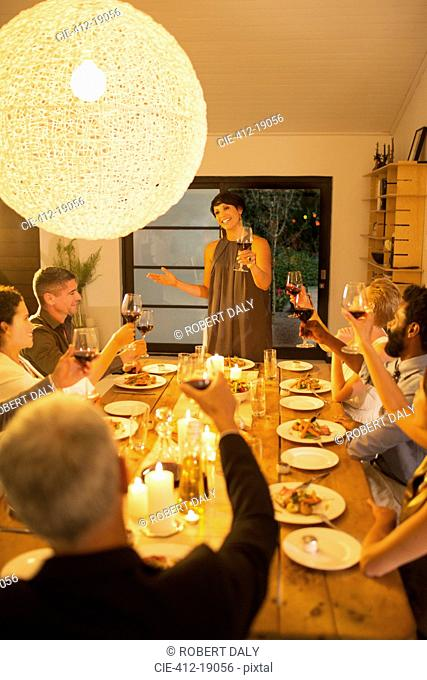 Woman giving toast at dinner party