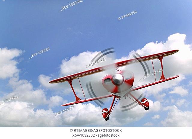 A red biplane flying in a blue cloudy sky