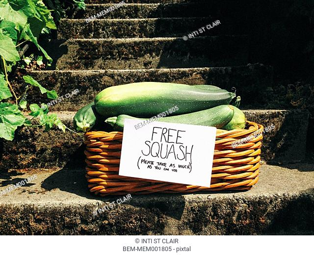 Basket of free squash on concrete staircase