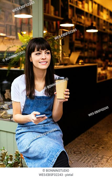 Smiling woman sitting at entrance door of a store holding cell phone and takeaway coffee