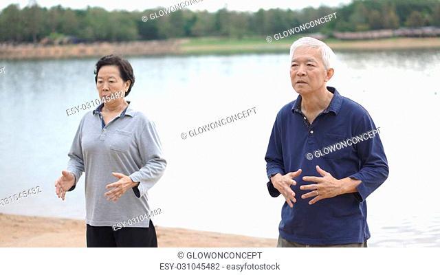 Asian Senior Elderly couple Practice Taichi, Qi Gong exercise outdoor next to the lake