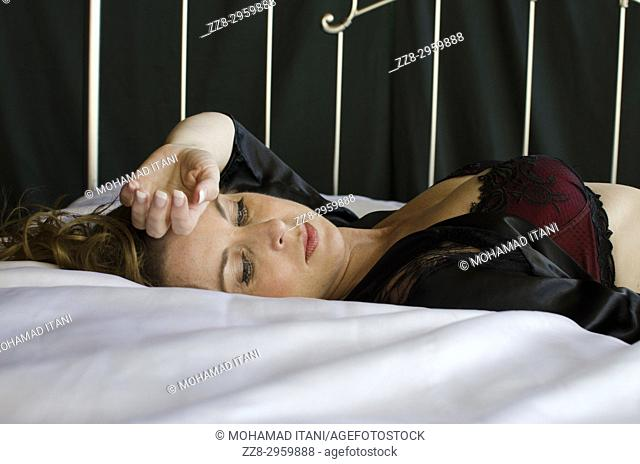 Sad woman laying down in bed hand over forehead