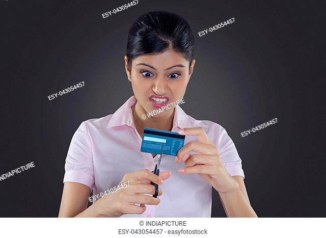 Businesswoman cutting credit card with scissors