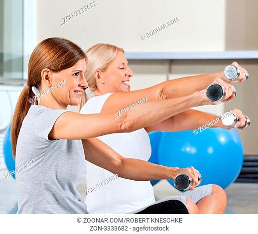 Zwei ältere Frauen machen Hanteltraining im Fitnesscenter