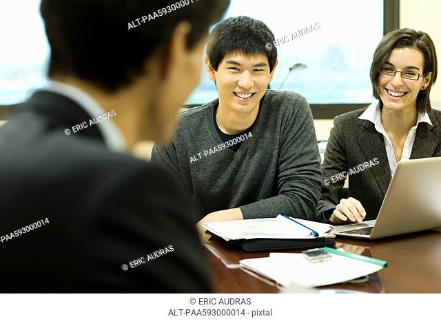 Executives in meeting, smiling at each other
