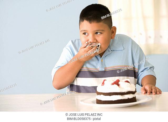 Hispanic boy eating cake with hand