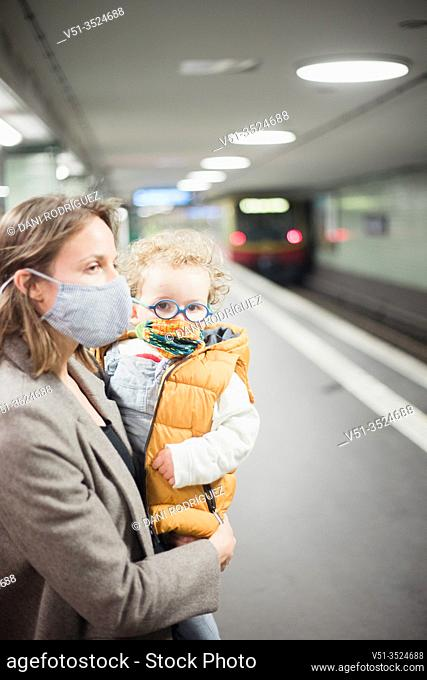Mother and son taking public transportation with mask during Corona days