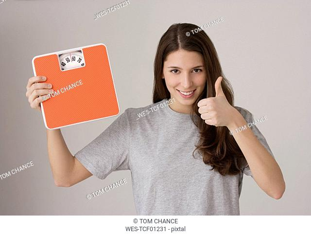 Young woman 16-17 holding Scales, thumbs up
