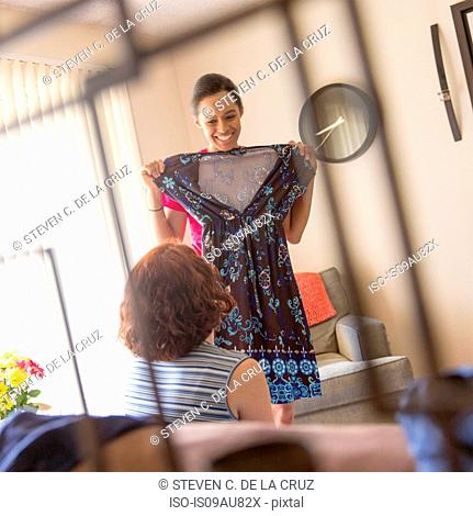 Young woman in living room showing friend dress
