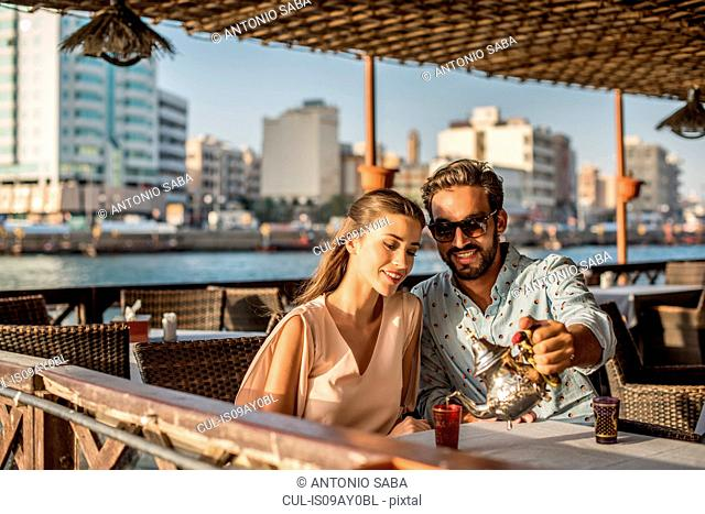 Romantic couple pouring tea at Dubai marina cafe, United Arab Emirates