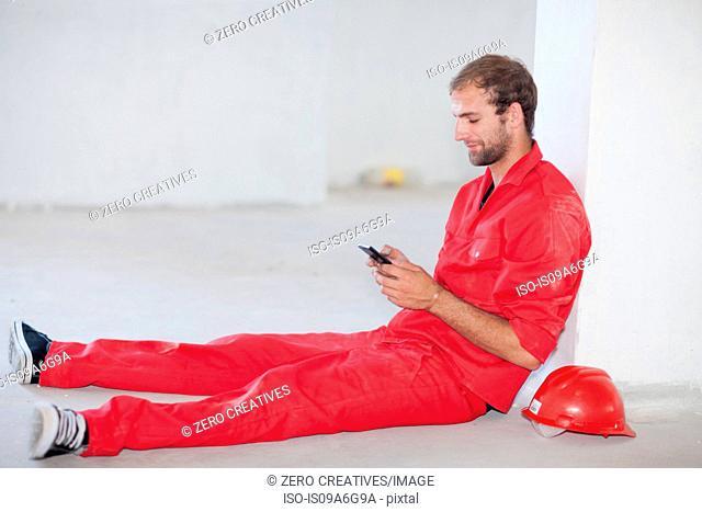 Construction worker sitting on floor taking a break