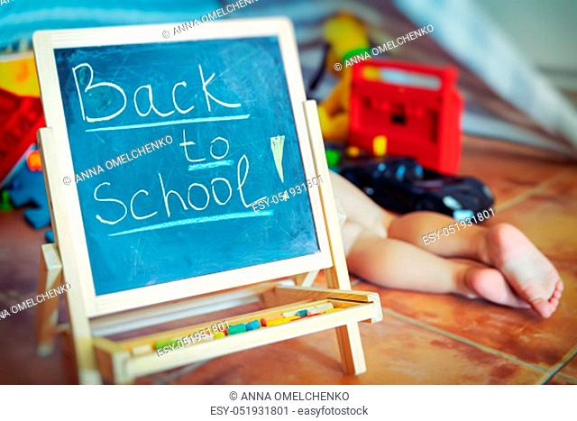 """Chalkboard with written words """"""""back to school"""""""" in the playroom, little boy lying down on the floor and playing, child plays and learns at the same time"""