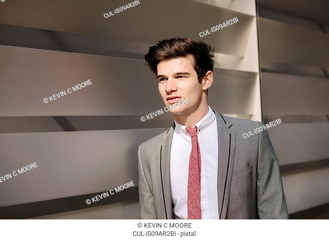 Young city businessman walking outside office
