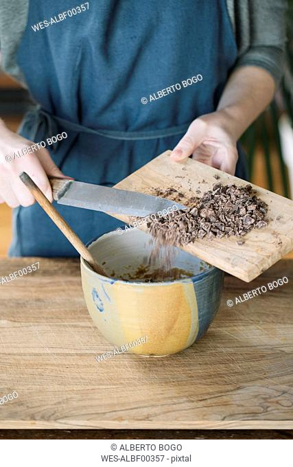 Woman preparing batter for homemade vegan chickpea cookies with bitter chocolate, partial view