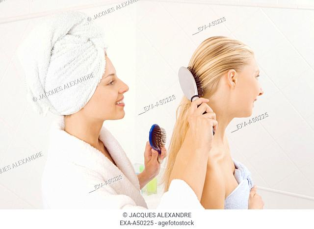 Close-up of two young girls combing their hair