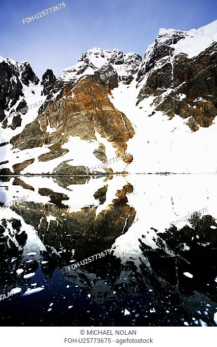 Reflections and snow covered mountains in Lemaire Channel in Antarctica