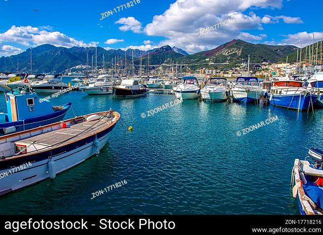 Amazing sunny day oin October in harbor of Salerno : pleasure boats and fishing boats. Behind - Salerno town,          mountains and famous amalfi coast