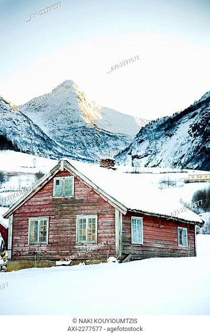 Traditional red wooden building in the village with sun setting over the mountains in the winter with snow; Ortnevik, Sognefjord, Norway