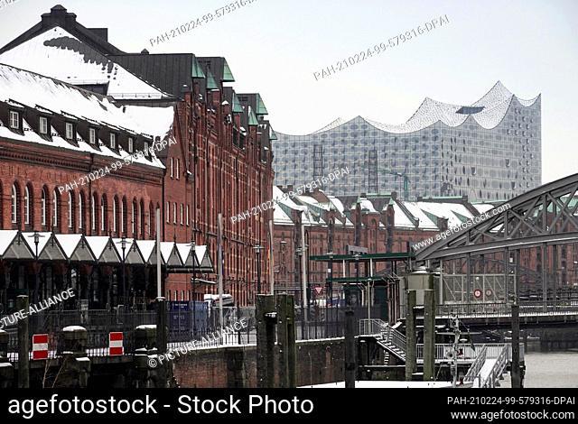 01 February 2021, Hamburg: Houses of the historic Speicherstadt on the Zollkanal against the backdrop of the Elbphilharmonie