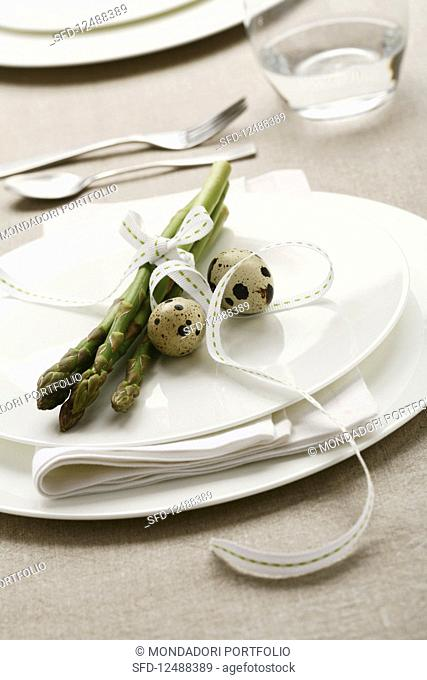 Spring plate decoration with green asparagus and quail's eggs
