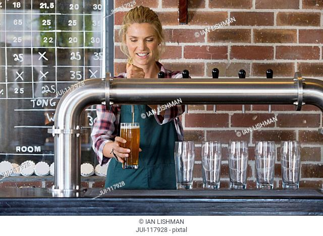Female Bartender Pouring Pint Of Beer Behind Counter