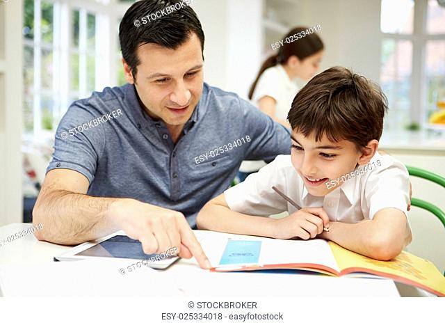 Father Helping Son With Homework Using Digital Tablet