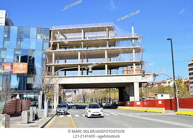 Building under construction, car, street, blue sky. Plaça Europa, Plaza Europa, District VII, Gran Via, Hospitalet de Llobregat, Barcelona province, Catalonia